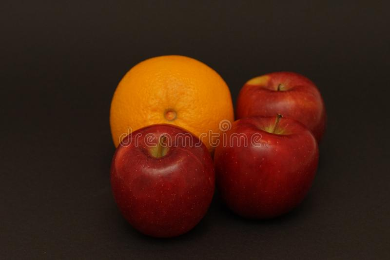 Red apples and orange on black background. Food photography. apple and orange capture in flash light stock images