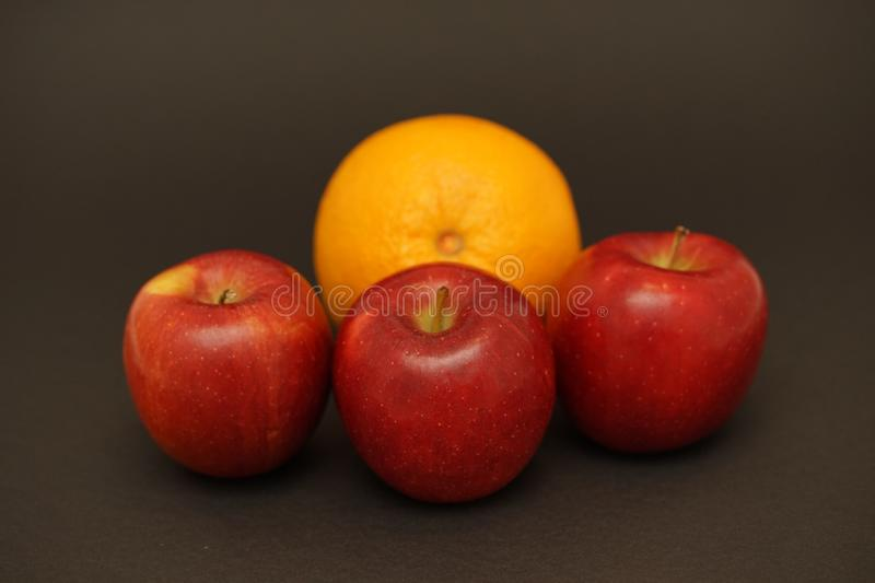 Red apples and orange on black background. Food photography. apple and orange capture in flash light stock photography