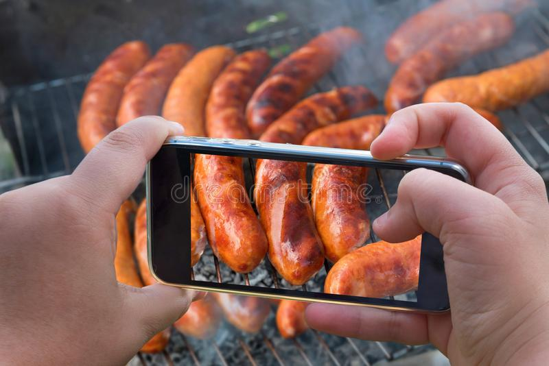 Food photography of baked sausages, meat. Photo of baked meat, shish kebabs with smartphone. Hands taking photo grilled fresh meat. With smartphone stock photo