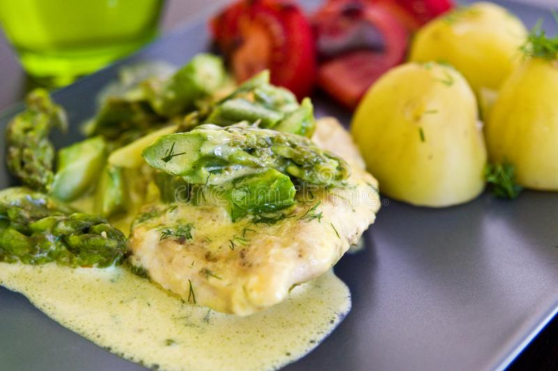 Food photography: chicken breast meat with asparagus and cream sauce royalty free stock photos