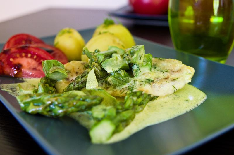 Food photography: chicken breast meat with asparagus and cream sauce royalty free stock photo