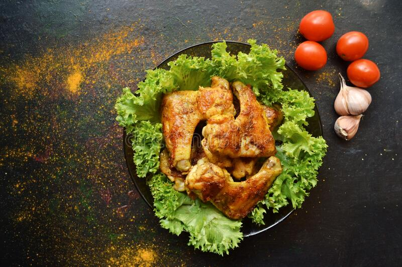 Food photography. Chicken wings with lettuce on a black background. Appetizing grilled meat, barbecue. Tasty dinner. Chicken wings. Food photography. Chicken royalty free stock photography
