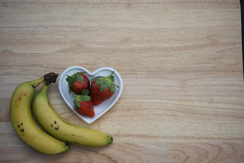 Food photography image of healthy red strawberries in a white love heart shape dish with bananas on wood background. Fresh juicy ripe red strawberry with green royalty free stock photography