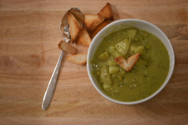 Food photography image of home made broccoli pea potato soup in white bowl with love heart shape toast on rustic wood background royalty free stock photos