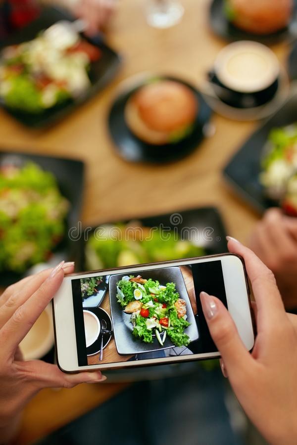 Food Photography On Smart Phone In Restaurant. Closeup Female Hands Making Photo Of Salad On Mobile Phone In Cafe. High Resolution royalty free stock photo