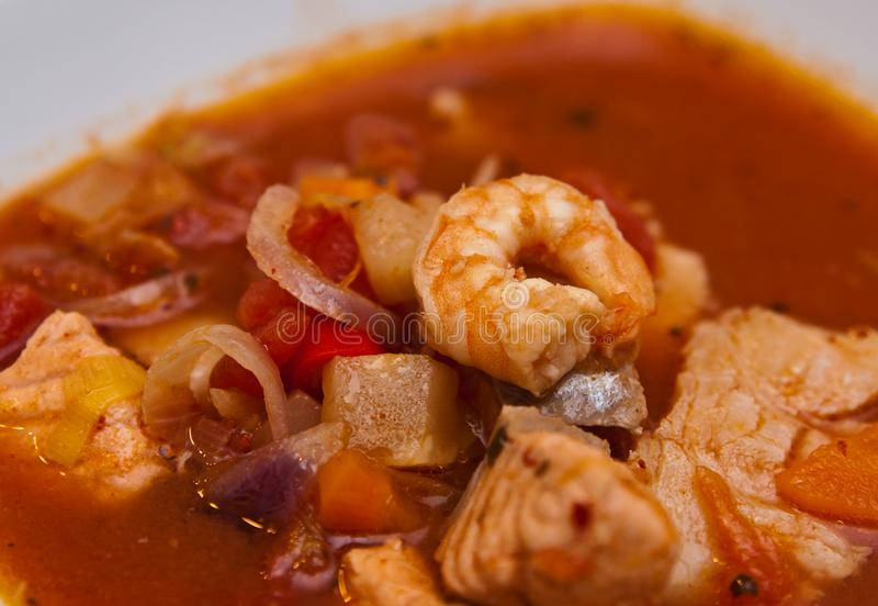 Fish soup with cod and prawns. Food photography: a spicy red fish soup with cod, paprika, spices and prawns or shrimps. Whole series with sebczseries1013 keyword royalty free stock photography