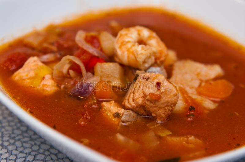 Fish soup with cod and prawns. Food photography: a spicy red fish soup with cod, paprika, spices and prawns or shrimps. Whole series with sebczseries1013 keyword stock photos