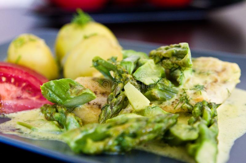 Food photography: chicken breast meat with asparagus and cream sauce stock images