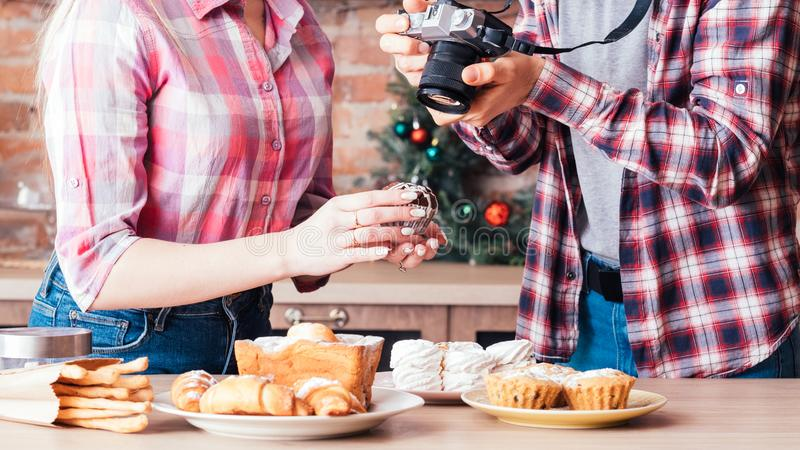 Food photography teamwork man woman photo cakes. Food photography. Teamwork. Man with women assitant taking photos of fresh homemade cakes and pastries stock images