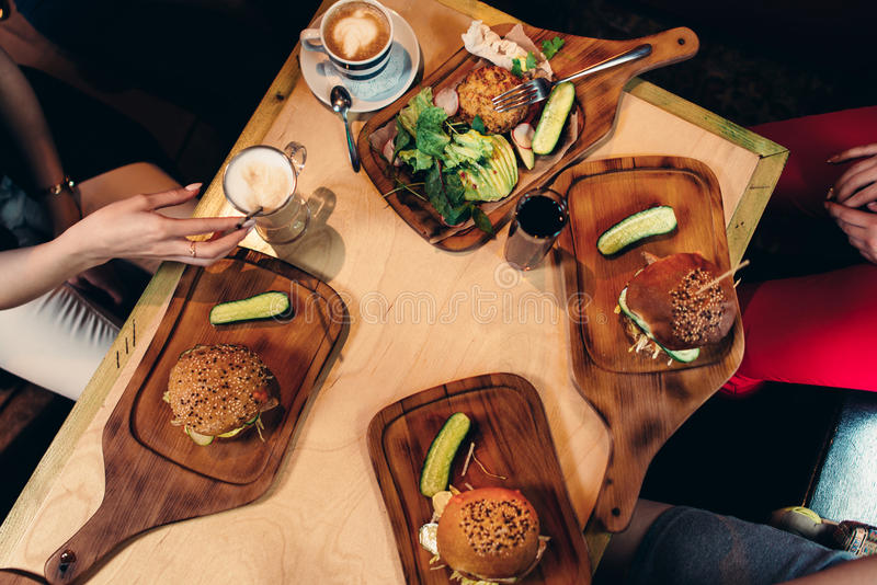 Food photography. Top view of hamburgers served with fresh vegetables, cucumbers on wooden boards in rustic style.  stock photo