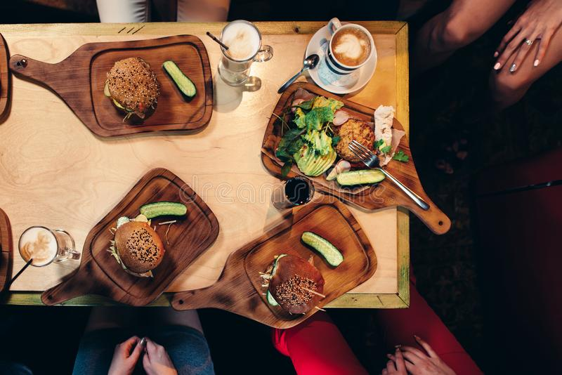 Food photography. Top view of hamburgers served with fresh vegetables, cucumbers on wooden boards in rustic style.  stock image