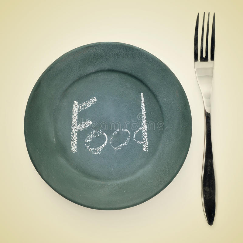 Food. Picture of a fork and a plate painted as a blackboard with the word food written in it with chalk on a beige background with a retro effect royalty free stock images