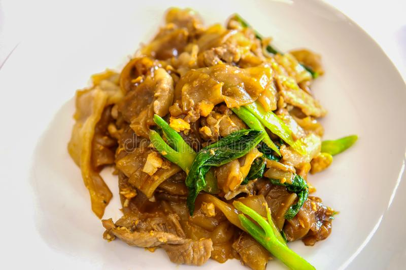 Food, Plate, Banana, Dinner, Kuala Lumpur. Stir fried flat noodle and pork with preserved soy bean paste in white on wooden table. Thai style food stock photos