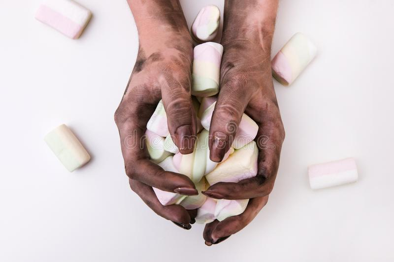 Food poisoning dirty hand hygiene germs. Food poisoning and poor hand hygiene. Dirty hands holding marshmallows on white background. Germs and insanitary stock photo