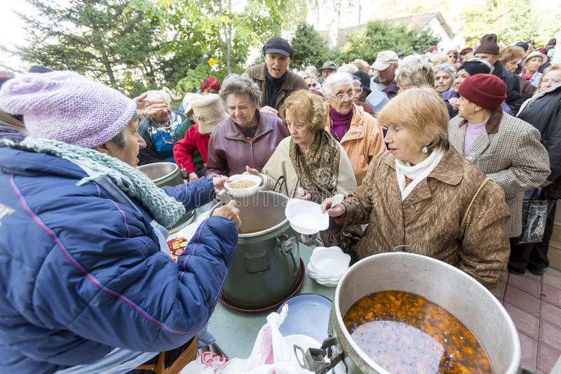 Food for the poor. Sofia, Bulgaria - October 26, 2015: Church personnel is giving food to the christian believers who have come to the morning prayer royalty free stock photos