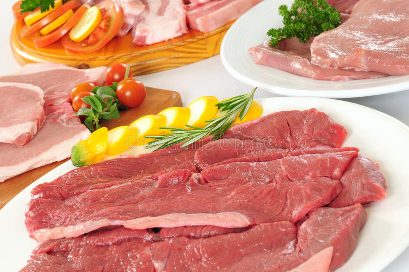 Food preparation. Variety of raw meats with vegetables royalty free stock images