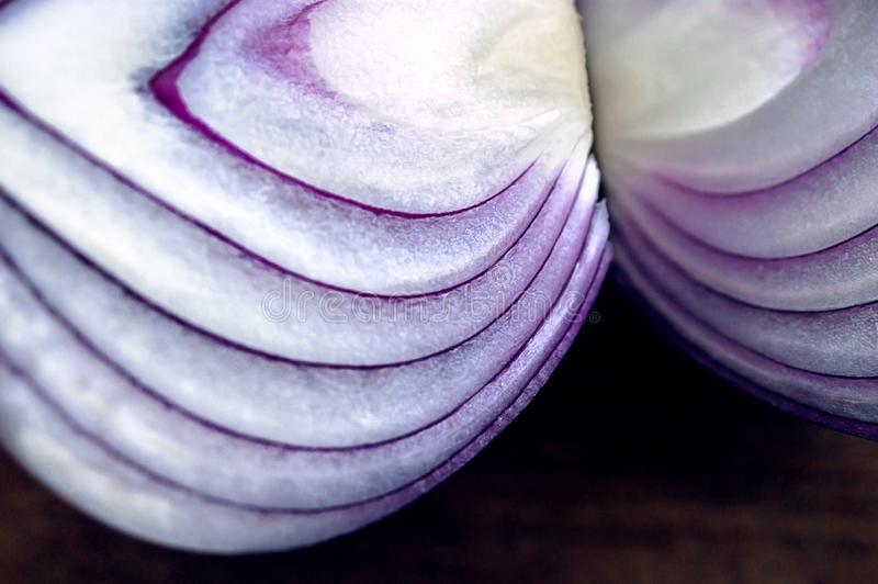 Food preparation, cooking concept: chopped and peeled fresh red onions on rustic wooden background stock image