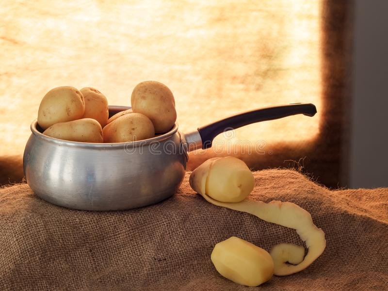Food preparation, peeling potatoes backlit by window, rustic setting still life with saucepan, hessian aka jute. Food preparation, peeling potatoes backlit by a stock photo