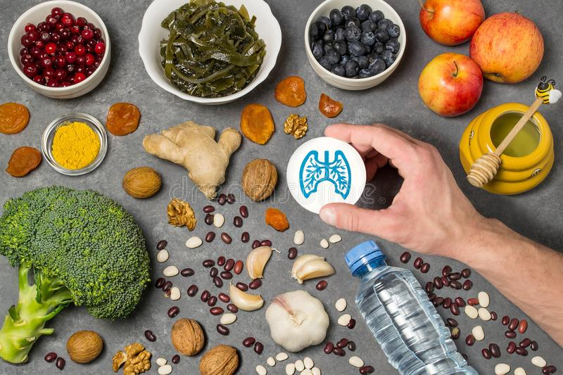 Food products useful for lungs. Set of natural food products are sources of vitamins and minerals. Man`s hand holds tag with homemade application from paper stock photography