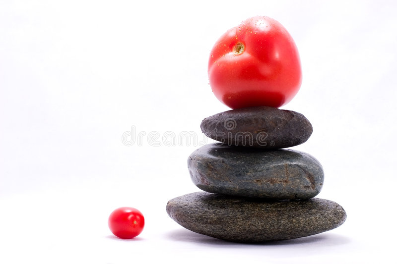 Food pyramid - tomato. Tomato on the top of zen stones pyramid in balance stock photography