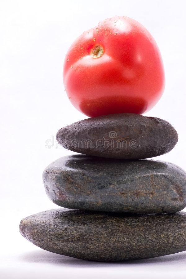 Food pyramid - tomato. Closeup of tomato on the top of zen stones pyramid in balance royalty free stock photography