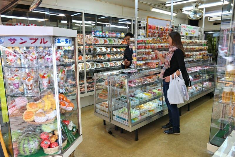 Food replica shop. TOKYO, JAPAN - DECEMBER 4, 2016: Person visits plastic food replica store in Kappabashi, Asakusa in Tokyo, Japan. Kappabashi Street is known stock image