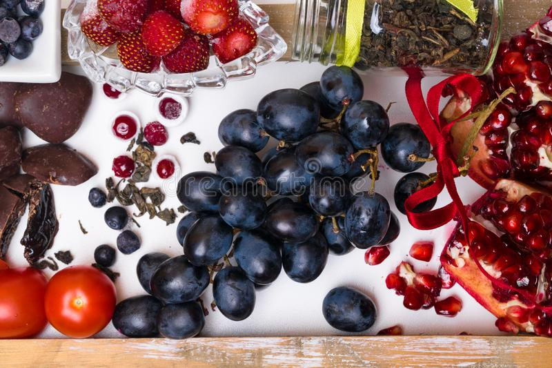 Food rich with resveratrol, grapes, plums, strawberry, dark chocolate,pomegranate, cranberry, green tea, tomatoes, blueberry. Food rich with resveratrol, grapes royalty free stock photos