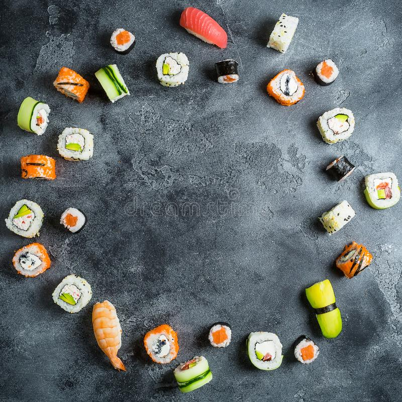 Food round frame made of set of Japanese food on dark background. Sushi rolls, nigiri, raw salmon steak, rice and avocado. Flat la stock image
