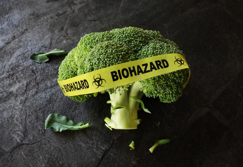 Food safety concept. Yellow Biohazard tape on a piece of broccoli -- food safety concept stock photography