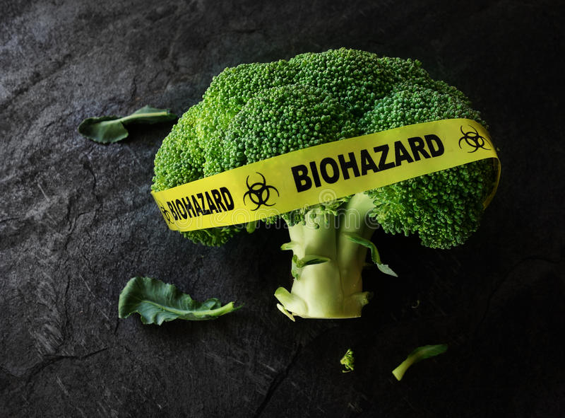 Food safety or contamination concept. Yellow Biohazard tape on a piece of broccoli -- food safety concept royalty free stock image