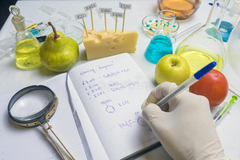 The food safety inspector is testing fruit from the market. Notebook with research report and blue pen on the lab table. Food safety inspector testing fruit from stock image