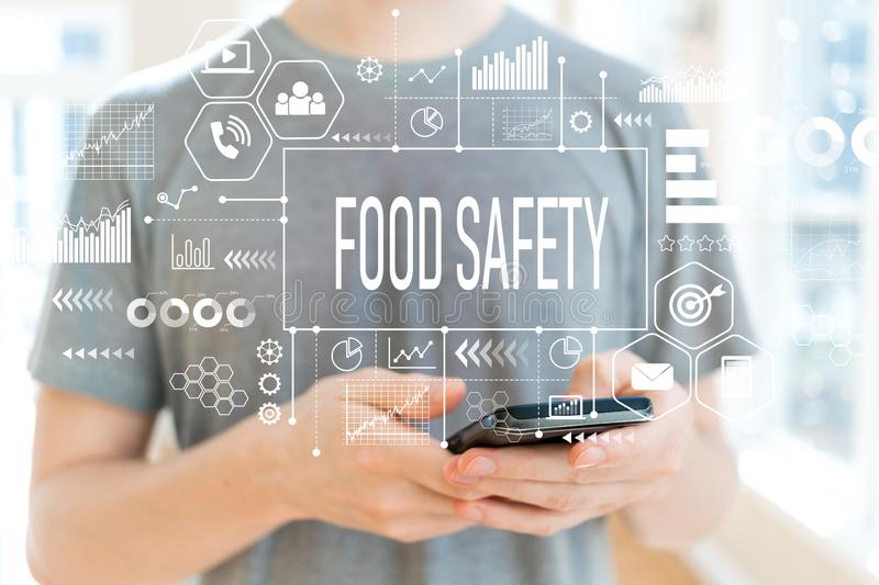 Food safety with man using a smartphone. Food safety with young man using a smartphone royalty free stock photo