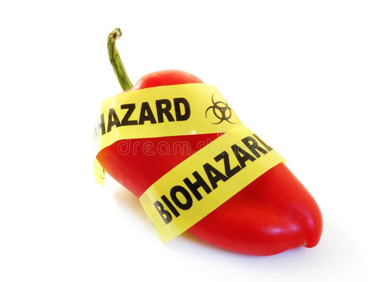 Food safety warning. Red pepper with bio-hazard tape.food safety concept royalty free stock photos