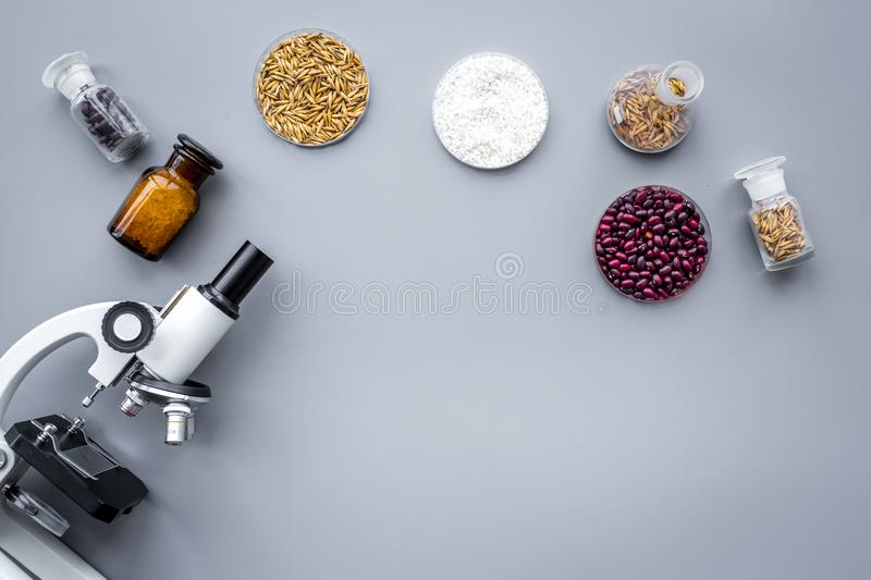 Food safety. Wheat, rice and red beans near microscope on grey background top view copyspace stock photo