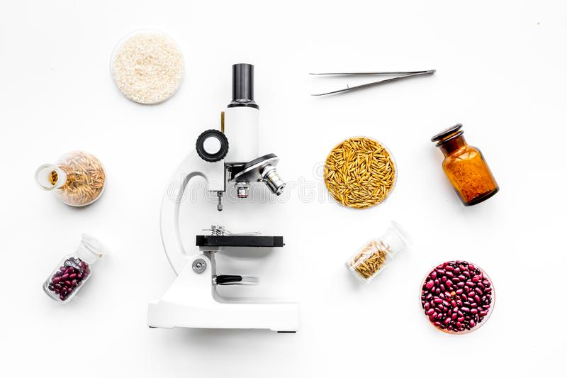 Food safety. Wheat, rice and red beans near microscope on white background top view stock photography