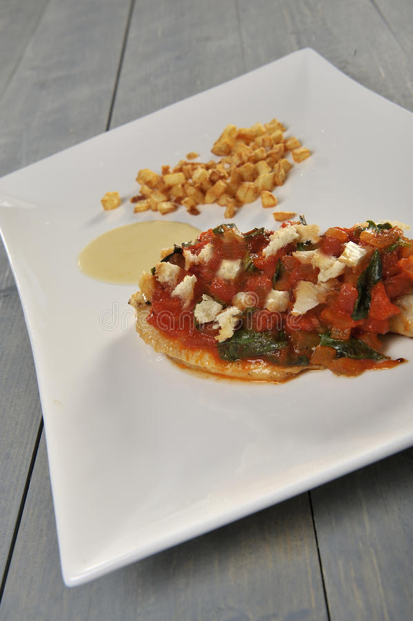 Food sea bass. Sea bass covered with tomatoes, basil, onion on a plate with potatoes and sauce stock images