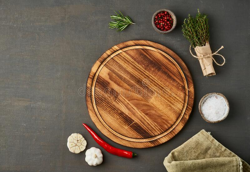 Food seasoning background. Menu, recipe, mock up. Round wooden cutting board on dark backdrop stock image