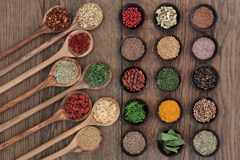 Food Seasoning. Herb and spice food seasoning selection in wooden spoons and bowls over oak wood background stock photography