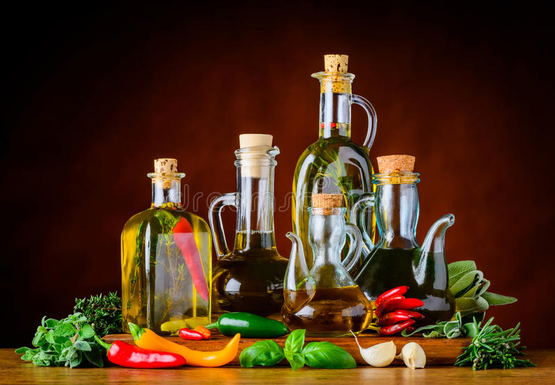 Food Seasoning Oil and Green Herbs. Food Seasoning virgin olive oil, green cooking herbs and pepper in still life stock images