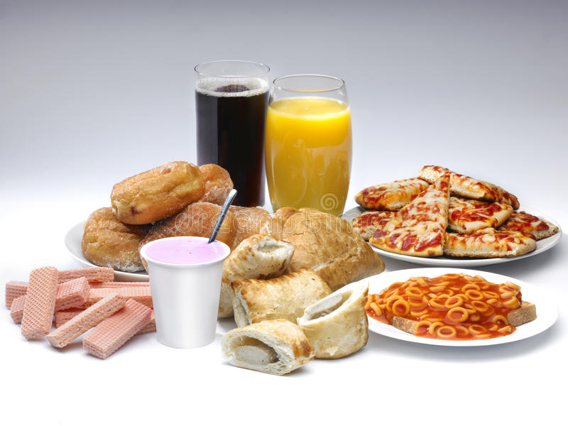 Food. A selection of processed food and drink on a white background including pIzza, cola, buscuits and sausage rolls royalty free stock image