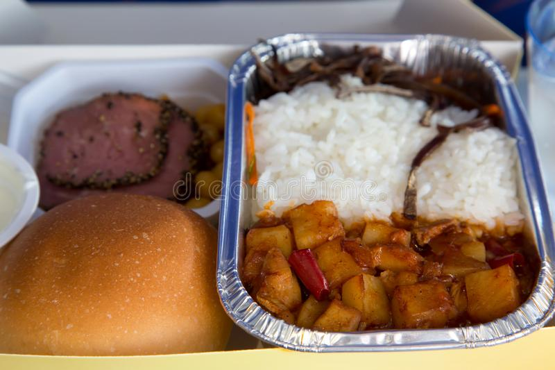 Food served in a passenger aircraft during the flight. Meal on t. He tray. Salad, meat appetizer, bread bun. Hot dish in the aluminum lunch box: chicken, rice stock photography
