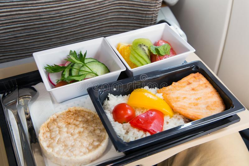 Food served in a passenger aircraft. In flight meal on the tray. Salad, butter and bread, fruits. Hot dish in the lunch box: salmon fish, rice and vegetables stock images