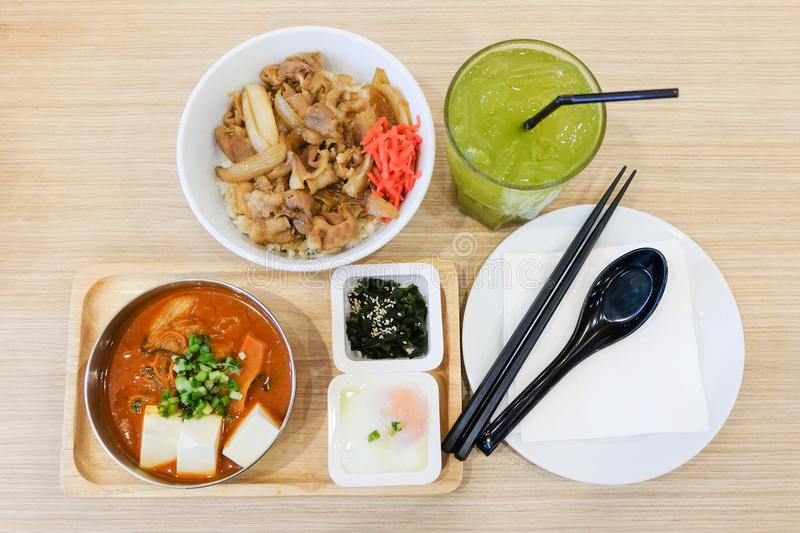 Food set consists of rice with grilled pork teriyaki, spring onion & carrot on top bowl serve with tofu & cabbage soup stock photo