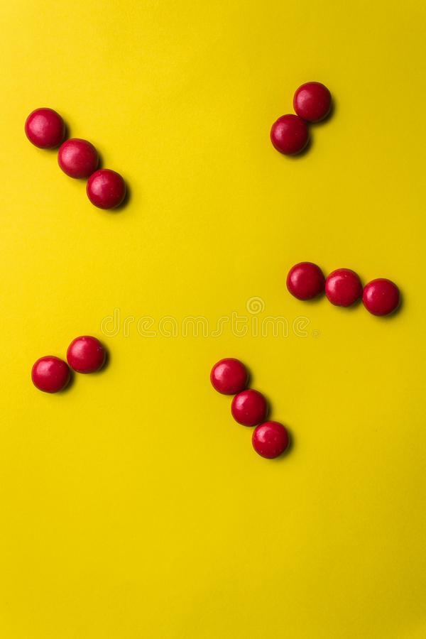 Red candy forming an abstract figure on a yellow background. stock image