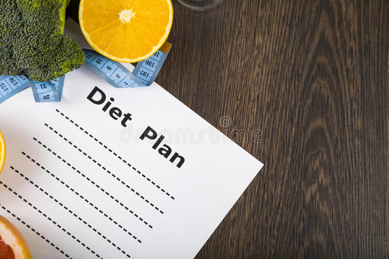 Food and sheet of paper with a diet plan on a dark wooden table. stock photo