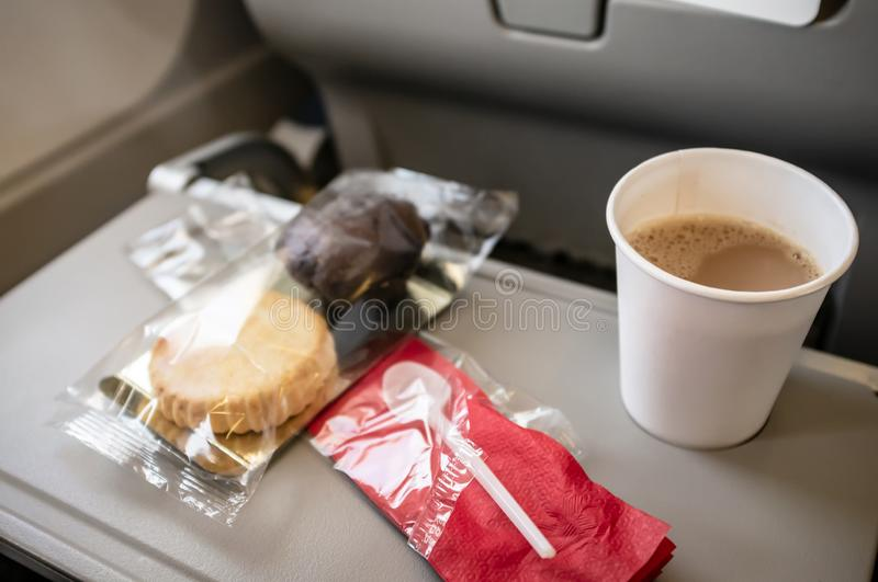 Food or a small snack in an airplane on rear seat table, in economy class. Baking in packaging and coffee in a plastic cup royalty free stock photography
