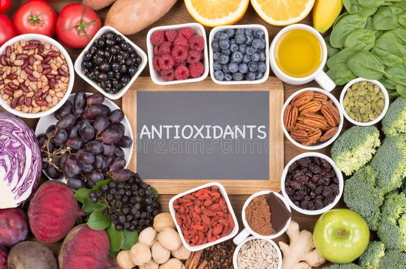Food sources of natural antioxidants such as fruits, vegetables, nuts and cocoa powder. Antioxidants neutralize free radicals royalty free stock photography