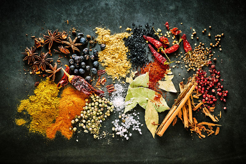 Food still life of aromatic and pungent spices. Food still life of aromatic and pungent culinary spices for Asian cuisine with acai berries and bay leaves on a royalty free stock photo