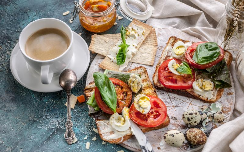 Food still life: cup of coffee, Italian toasts with cheese, tomatoes, basil, quail eggs. Ideas for a tasty and healthy breakfast royalty free stock photo