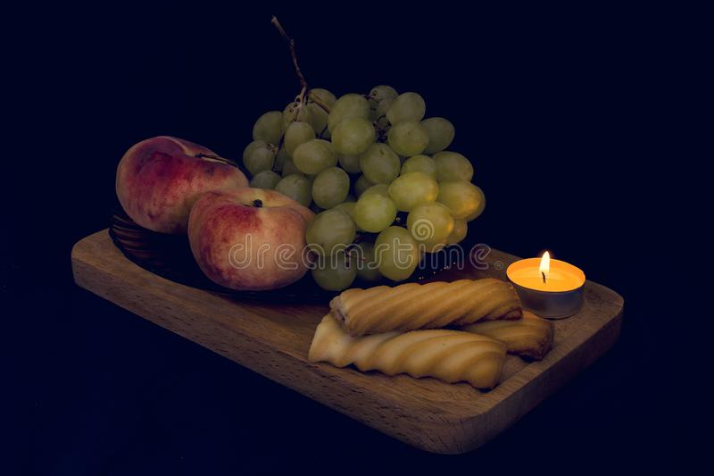 Food still life photography with pitches, grapes and candlelight. stock photos